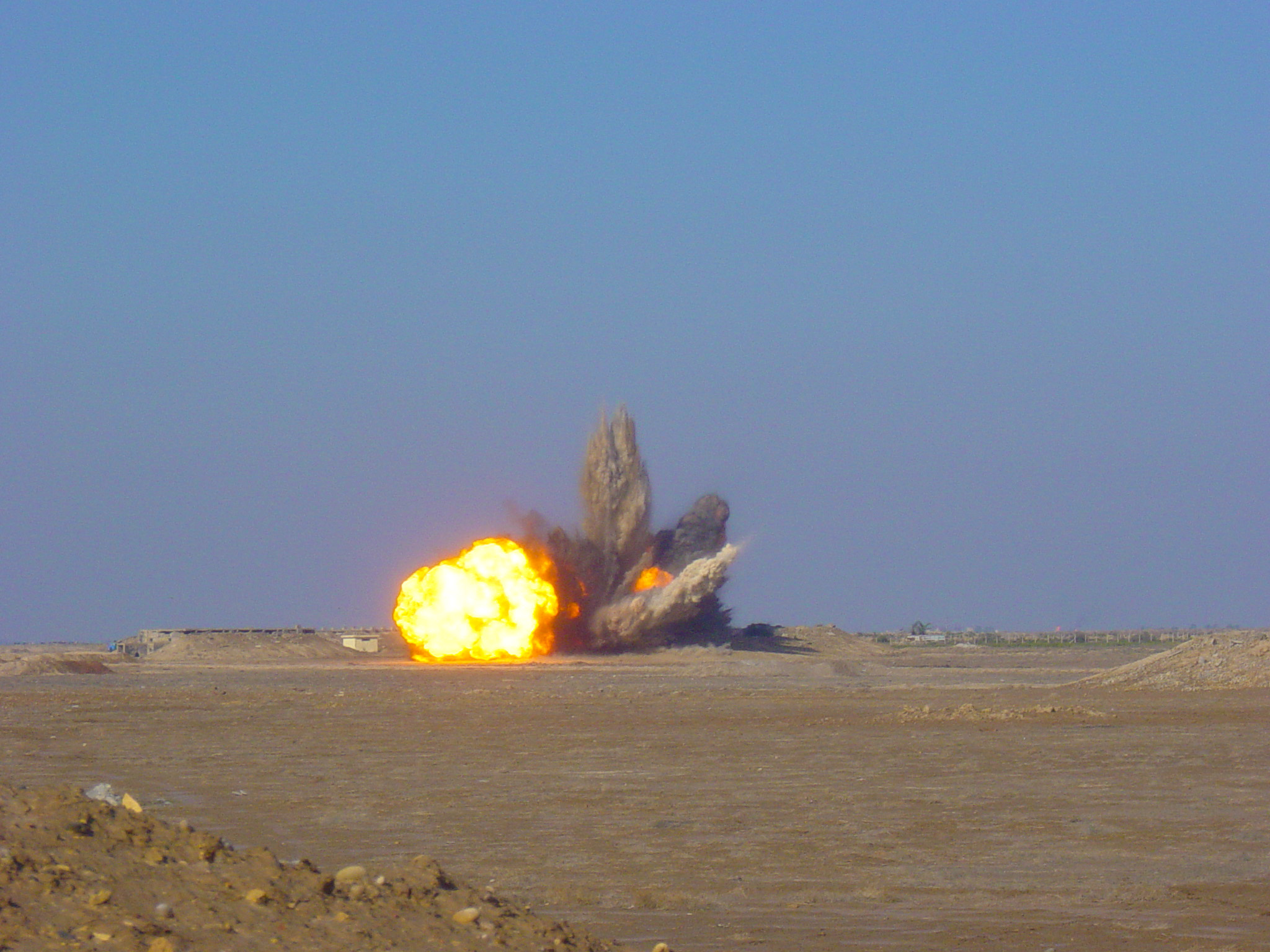 Controlled detonation of a prepared cache of munitions in the desert